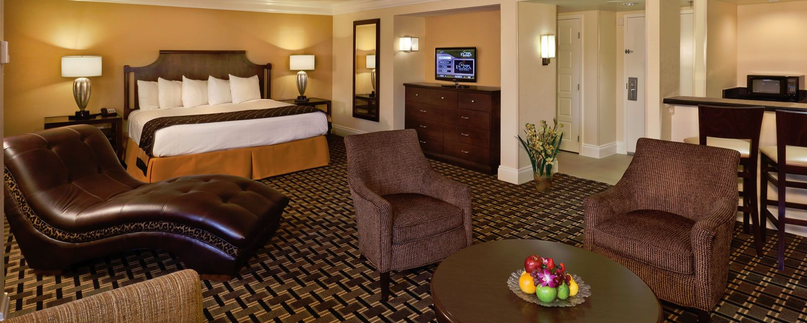Junior Suites with bed, chairs, tvs, and table with fruit