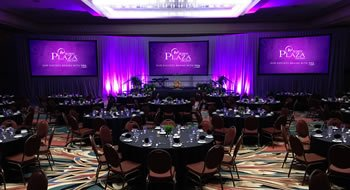 Ballroom set up for a meeting with purple lighting, black table cloths