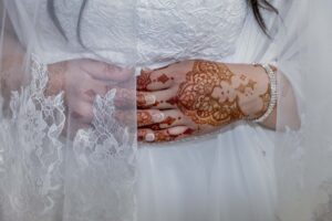Close up shot of a bride in a white lace wedding gown and lace veil. Her hands, intricately decorated in henna, are folded over her midsection.